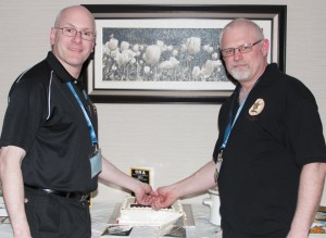 Brett Irick, left, and Robb McPherson cut the cake at the welcome reception on the first day of the ONA convention.