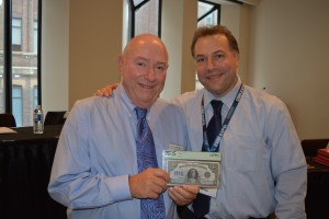 Auctioneers Geoff Bell, left, and Brian Bell display the 1924 Dominion of Canada $5 Queen Mary banknote. In superb uncirculated condition. the banknote has a auction estimate of $25,000 to $27,000.