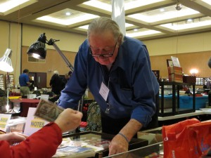 Nick Cowan, owner of the Coin Collector, helping a collector find a banknote.
